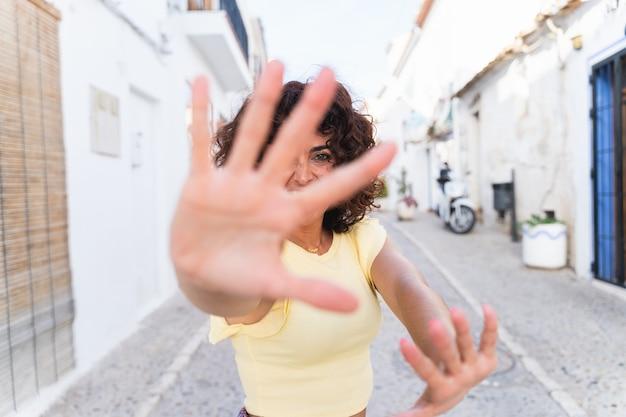 Horizontale weergave van een vrouw die zich voor de camera verstopt. stop en vecht concept. onherkenbare krachtige vrouw