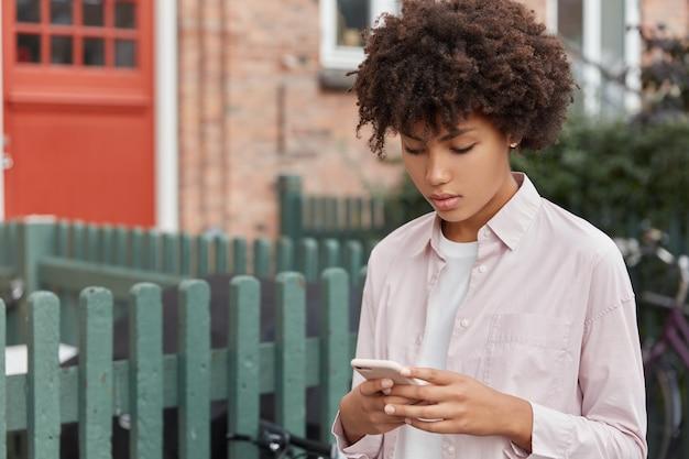 Horizontale weergave van ernstige geconcentreerde schattig afro meisje in stijlvol shirt