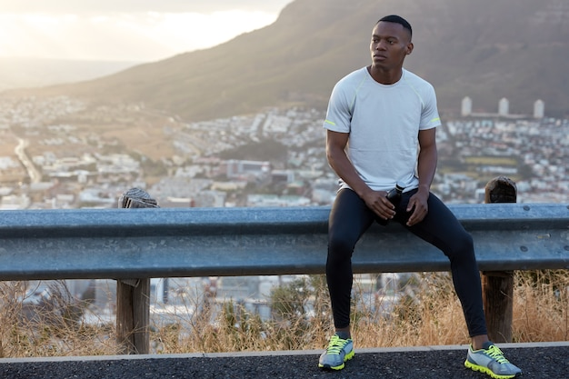 Horizontale weergave van gemotiveerde zwarte man voelt zich ontspannen en tevreden na joggingoefeningen, kijkt peinzend opzij, houdt fles met drankje vast, gaat tegen rots staan met kopie ruimte aan linkerkant voor tekst