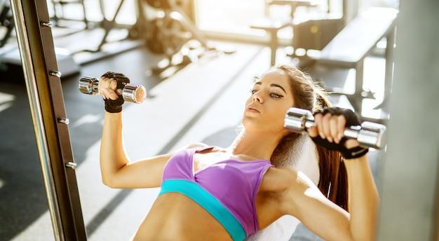 Horizontale weergave van gerichte gemotiveerde slanke actieve gezonde jonge vrouw borst oefening met kleine halters op de bank in de zonnige moderne sportschool close-up.