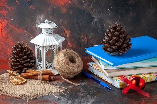 Horizontale weergave van gestapelde notebooks en pen bal van touw kaneel limoenen conifer kegels op donkere achtergrond