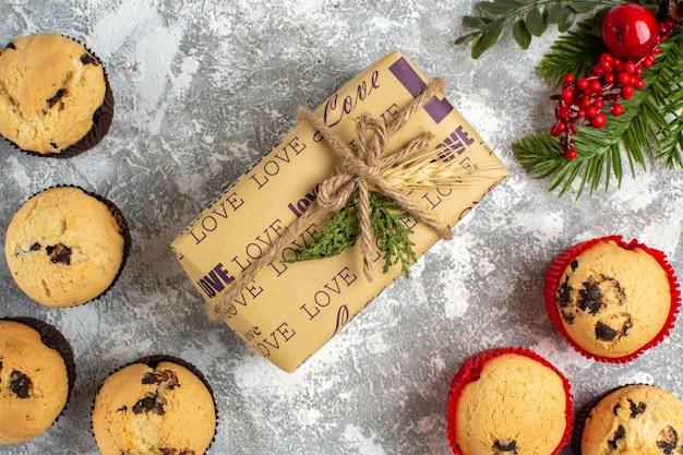 Horizontale weergave van heerlijke kleine cupcakes met chocolade en dennentakken naast cadeau op ijsoppervlak