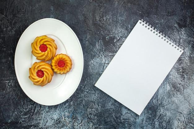 Horizontale weergave van heerlijke koekjes op een witte plaat en notitieboekje op donkere ondergrond