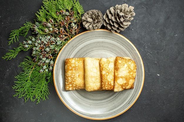 Horizontale weergave van heerlijke met vlees gevulde pannenkoeken op een witte plaat en coniferenkegel op zwarte achtergrond