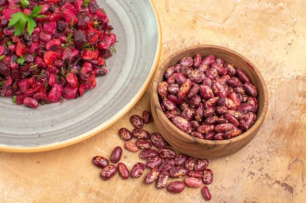 Horizontale weergave van heerlijke salade met rode biet en bonen en bonen binnen en buiten de pot op gemengde kleurenachtergrond