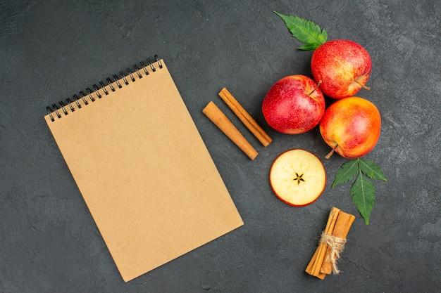 Horizontale weergave van hele en gesneden verse natuurlijke biologische rode appels met groene bladeren, kaneellimoenen en notitieboekje op zwarte achtergrond
