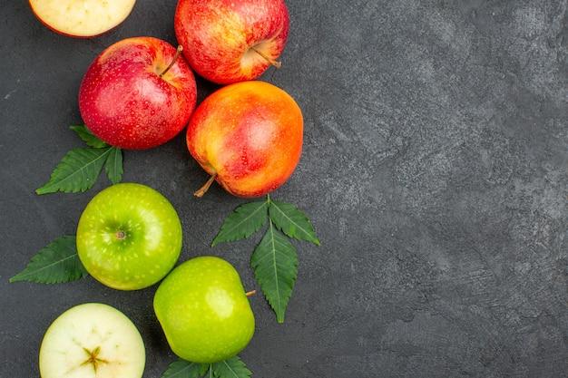 Horizontale weergave van hele en gesneden verse rode appels en bladeren aan de rechterkant op zwarte achtergrond
