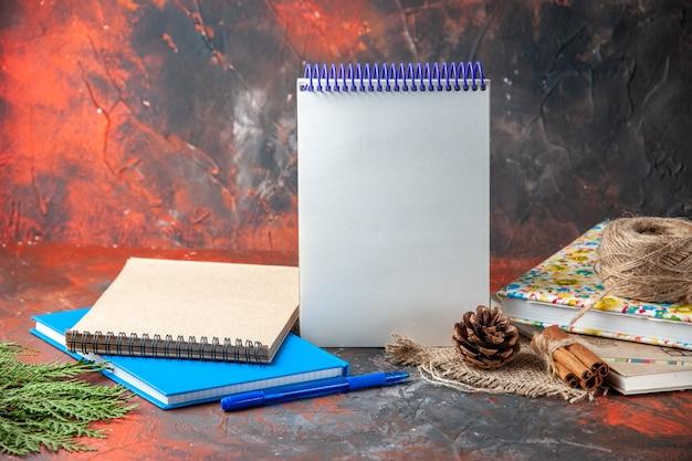 Horizontale weergave van kantoorbenodigdheden en pen kaneel limoenen conifer kegel op bruine handdoek op donkere achtergrond