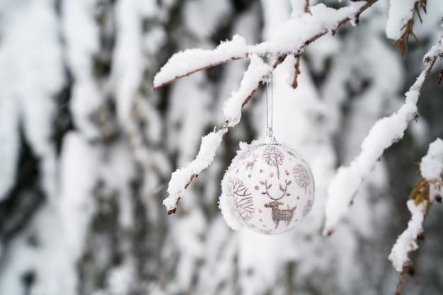 Horizontale weergave van kerst ornament met een rendier opknoping van een pijnboom bedekt met sneeuw buitenshuis.