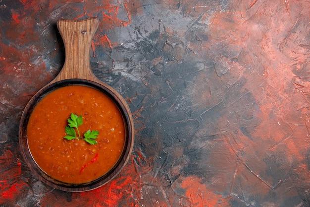 Horizontale weergave van klassieke tomatensoep op een bruine snijplank op gemengde kleurentafel