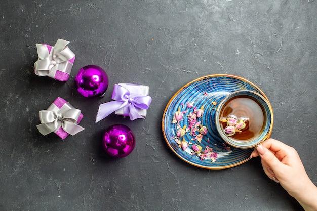 Horizontale weergave van kleurrijke geschenken en decoratieaccessoires een kopje zwarte thee op donkere achtergrond