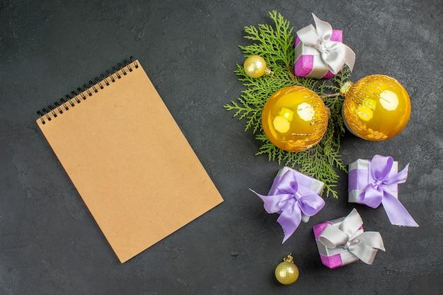 Horizontale weergave van kleurrijke geschenken en decoratieaccessoires en notitieboekje op donkere achtergrond