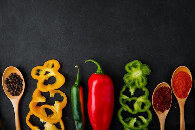 Horizontale weergave van lepels kruiden en paprika's op zwarte achtergrond met kopie ruimte