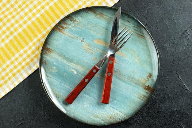 Horizontale weergave van maaltijdbestek in kruis op een blauw bord en gele gestripte handdoek op een donker oppervlak