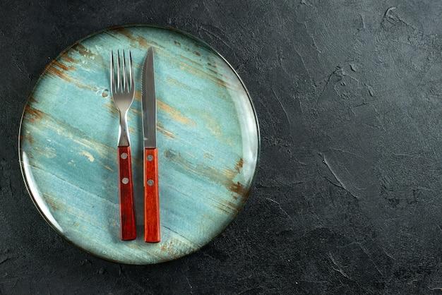 Horizontale weergave van maaltijdbestek op een blauw bord aan de rechterkant op een donkere ondergrond