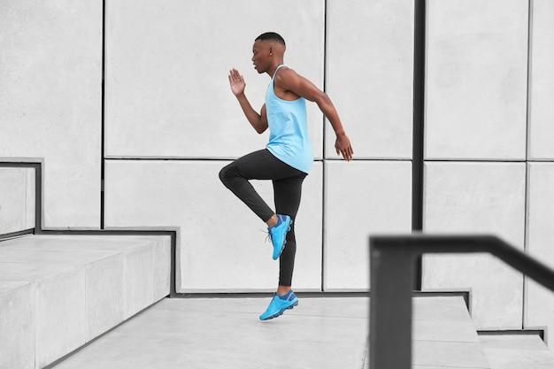 Horizontale weergave van mannelijke atleet gekleed in activewear, heeft cardio rennen trap bereidt zich voor op joggen op lange afstand maakt stappen of springt hoog. afro-amerikaanse man in t-shirt, legging, trainers