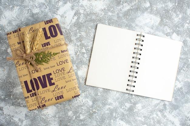 Horizontale weergave van mooi groot ingepakt cadeau en open notitieboekje op ijsoppervlak