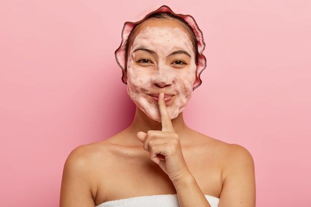 Horizontale weergave van mooie aziatische dame met schuim op gezicht, reinigt van vuil, wil een frisse blik hebben, maakt stilte gebaar, draagt een douchemuts, ziet er gelukkig uit. netheid en hygiëne concept