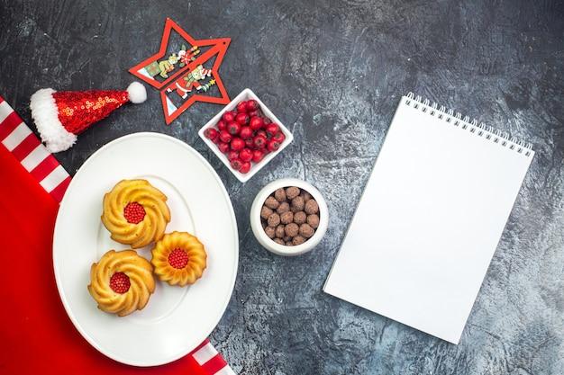 Horizontale weergave van notebook en heerlijke koekjes op een witte plaat op rode handdoek en kerstman hoed cornel en chocoltes in witte potten op donkere ondergrond