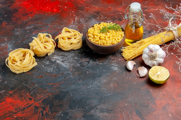 Horizontale weergave van ongekookte drie porties spaghetti en vlinderpasta's in een bruine kom en groene ui citroen knoflookolie fles op gemengde kleurentafel
