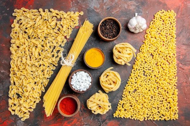 Horizontale weergave van ongekookte pasta in verschillende vormen en verschillende kruiden op zwarte tafel