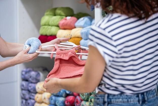 Horizontale weergave van onherkenbare jonge vrouw die kleding voor een pasgeboren baby winkelt