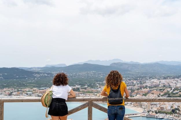 Horizontale weergave van onherkenbare vriendinnen bovenop de berg in javea. vakantie reizen concept.