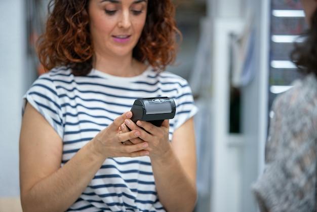 Horizontale weergave van onherkenbare winkelbediende die een creditcardterminal gebruikt