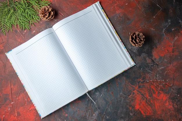 Horizontale weergave van open ongeschreven spiraalvormig notitieboekje en naaldboomkegels en sparrentak op donkere achtergrond