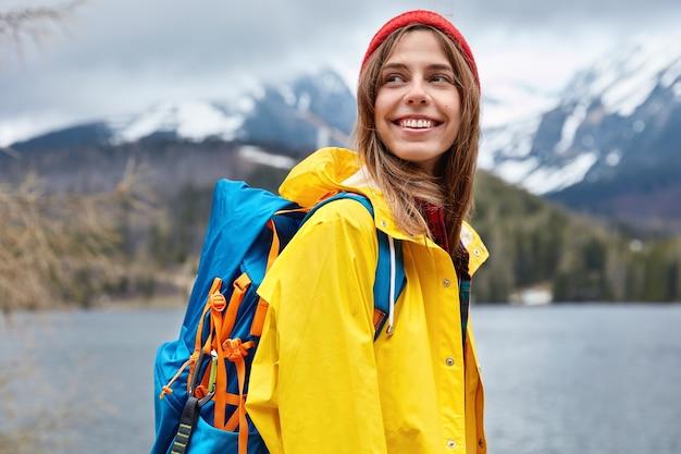 Horizontale weergave van optimistische europese vrouwelijke toerist kijkt gelukkig opzij, geniet van wandelen in de buurt van bergmeer, bewondert prachtige landschappen. mensen