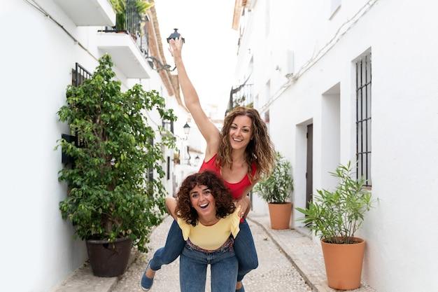 Horizontale weergave van paar vriendinnen die lachend een ritje op de rug geven. reisconcept in de zomer.