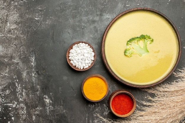 Horizontale weergave van romige broccolisoep in een bruine kom en verschillende kruiden op grijze tabelbeelden
