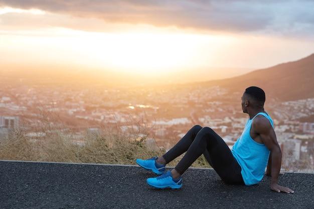 Horizontale weergave van rustgevende atletische man met gezonde lichaamsvorm, spieren op armen, zit op hoge heuvelweg, opzij gericht, bewondert majestueuze dageraad, frisse lucht, heeft training buiten. mensen, energieconcept