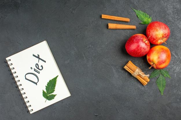 Horizontale weergave van spiraalvormig notitieboekje met dieetinscriptie en verse appels, kaneellimoenen op zwarte achtergrond