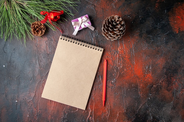 Horizontale weergave van spiraalvormige notebook pen conifer kegel cadeau en cadeau op donkere achtergrond