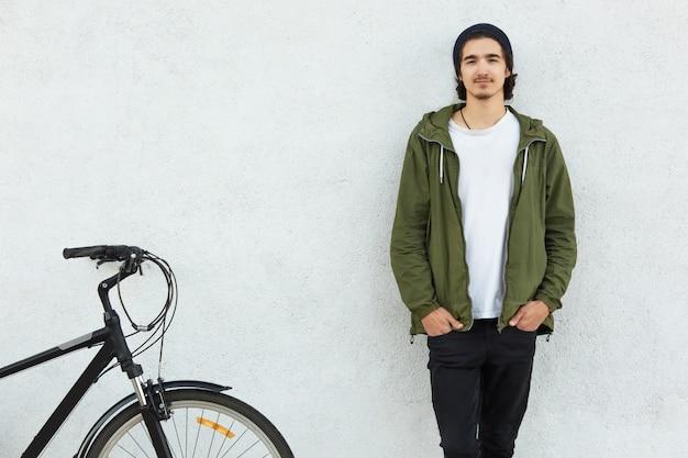 Horizontale weergave van stijlvolle man houdt handen in zakken van zwarte broek draagt groene jas, staat in de buurt van zijn fiets, houdt van fietsen