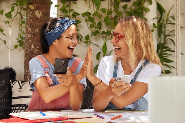 Horizontale weergave van succesvolle vrouwelijke partners van gemengd ras geven vijf aan elkaar, zijn het eens met een goed idee voor het maken van een project