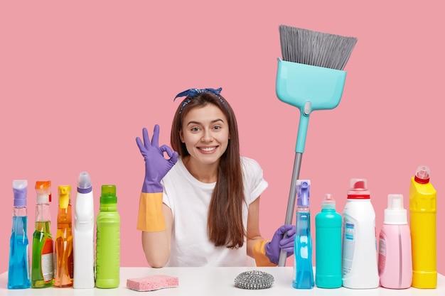 Horizontale weergave van tevreden huishoudster maakt ok gebaar, tevreden met resultaat van perfecte reiniging, gebruikt wasmiddelen van goede kwaliteit, glimlacht breed