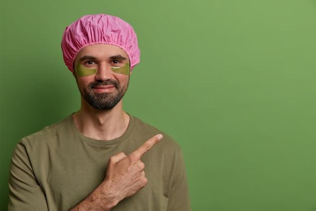 Horizontale weergave van tevreden ongeschoren man draagt roze badmuts, casual t-shirt, heeft ooghuidbehandeling, past collageenkussentjes toe om fijne lijntjes te verminderen, wijst naar lege ruimte, adverteert met een product