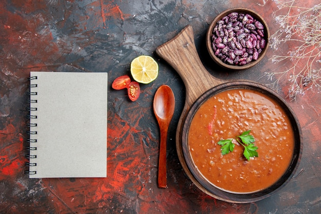 Horizontale weergave van tomatensoep bonen en notebook op snijplank op een gemengde kleurentafel
