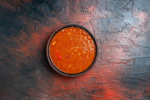 Horizontale weergave van tomatensoep in een bruine kom op gemengde kleurentafel