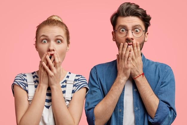 Horizontale weergave van verbijsterde jonge vrouw en man bedekken de mond met angst, hebben gezichtsuitdrukkingen verrast, ontdekken tragisch nieuws van de spreker, staan schouder aan schouder tegen roze muur