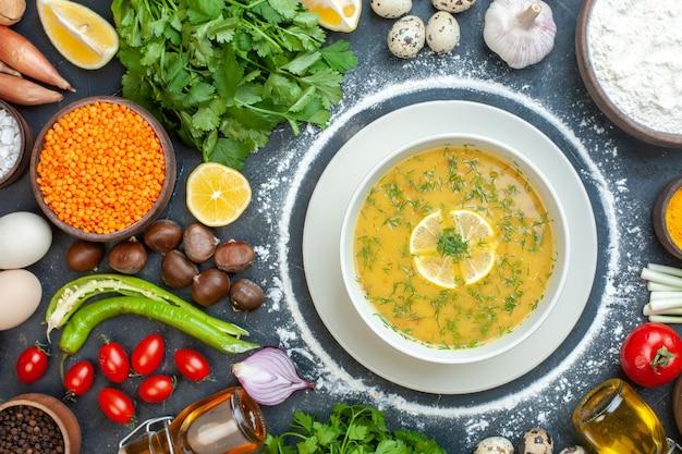 Horizontale weergave van verrukkelijke soep geserveerd met citroen en groen in een witte kom en bloem tomatenolie fles bloem groene bundels eieren op donker