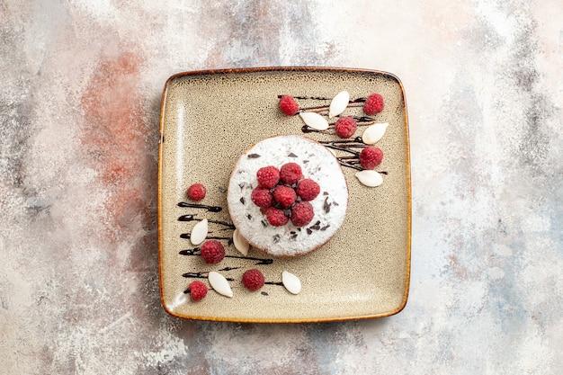 Horizontale weergave van vers gebakken cake met frambozen voor baby's op een bruin dienblad op witte tafel