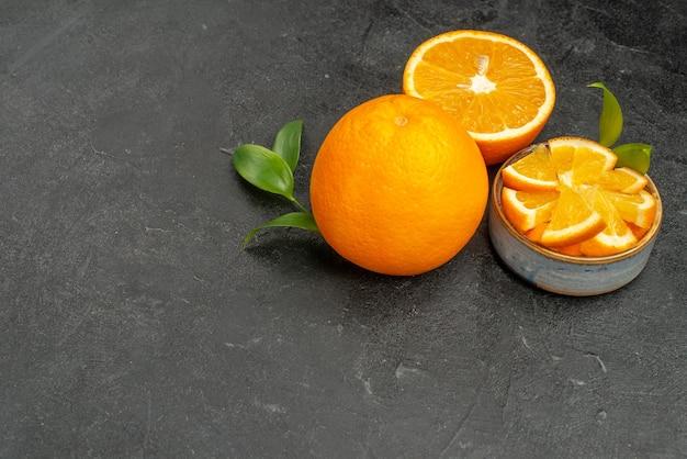 Horizontale weergave van vers gesneden citroen helften op hele citroenen op donkere tafel