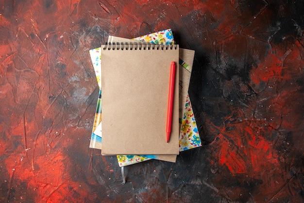 Horizontale weergave van verschillende gestapelde spiraalvormige notitieboekjes met pen op donkere achtergrond