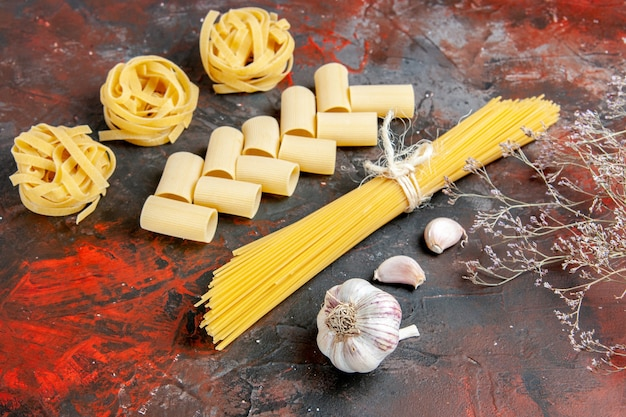 Horizontale weergave van verschillende soorten ongekookte pasta's en knoflook op zwarte tafel