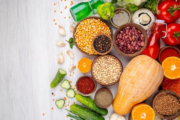 Horizontale weergave van verse bloemkool en verschillende voedingsmiddelen om te koken aan de rechterkant op witte tafel