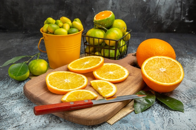Horizontale weergave van verse citrusvruchten met mes op houten snijplank op krant op grijze achtergrond