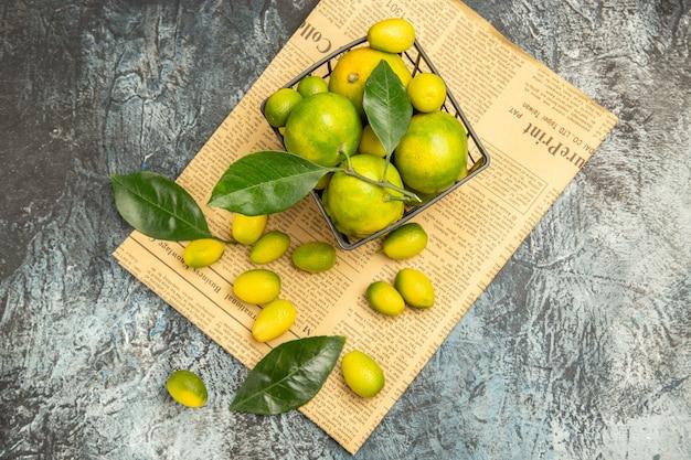 Horizontale weergave van verse kumquats en citroenen in een zwarte mand op kranten op grijze achtergrond